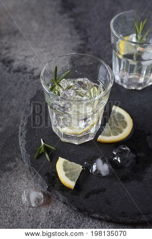 Cocktail with lemon sprig of rosemary and ice cubes