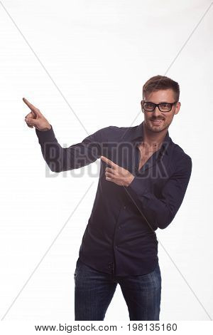 Young jocular man portrait of a confident businessman showing by hands on a gray background. Ideal for banners, registration forms, presentation, landings, presenting concept.