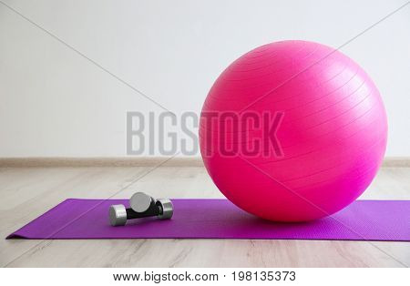 Rubber ball and dumbbells on mat