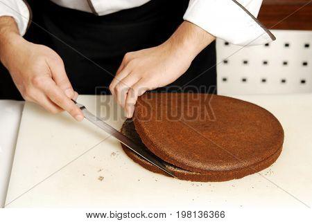 Male chef preparing cake on the kitchen board
