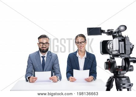 Two Smiling Newscasters With Papers Sitting In Front Of Camera, Isolated On White