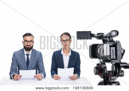 Two Newscasters With Papers Sitting In Front Of Camera, Isolated On White