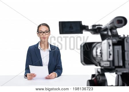 Beautiful Female Newscaster With Papers Sitting At Table And Looking At Camera, Isolated On White