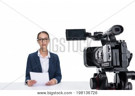 Attractive Female Newscaster With Papers Sitting In Front Of Camera, Isolated On White