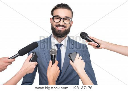 Journalists With Microphones Interviewing Smiling Handsome Businessman, Isolated On White