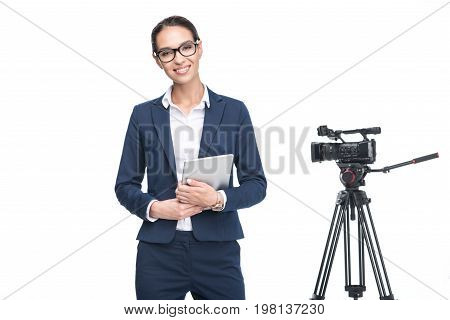 Smiling Female Television Reporter Using Digital Tablet Standing Near Video Camera, Isolated On Whit