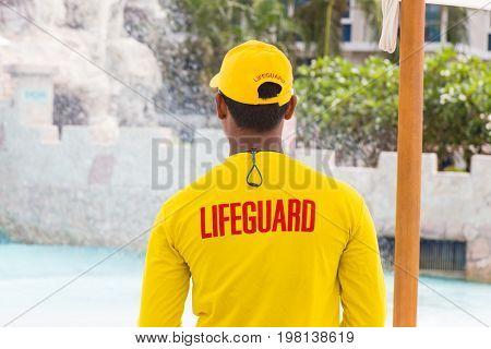 back of lifeguard man wearing yellow lifeguard shirt and cap standing on duty