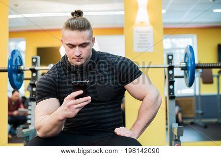 Handsome guy text messaging on his smartphone at gym