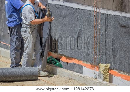 Workers Installing Wall Insulation