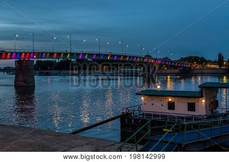 Night view of the Rainbow Bridge on the Danube River in Novi Sad Serbia with a pontoon of boats in front.