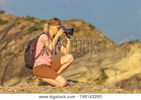 Nature woman photographer with camera takes picture outdoor. Caucasian female with backpack shooting on mountain top.Professional photographer takes photo of mountain landscape after hiking.Copy space
