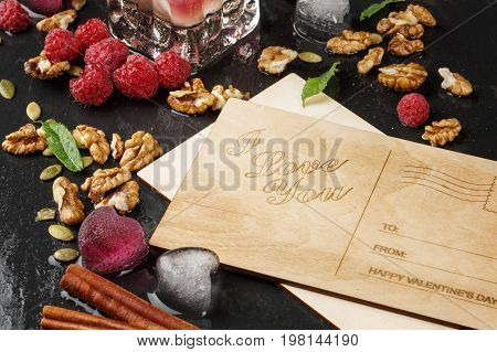 Close-up of a beautiful composition of romantic postcards, fruity hearts, cinnamon, and walnuts on a black wooden background. Pink raspberries and ice hearts next to a love note. Romance concept.