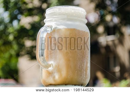 cold brewed ice coffee served in mason jar with froth