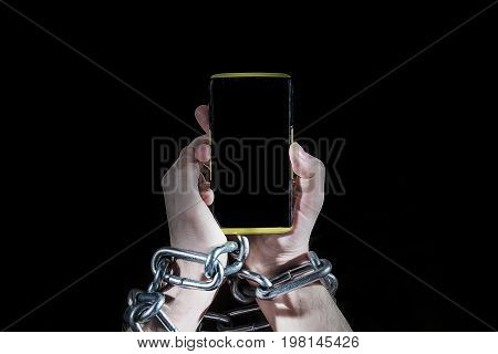 Hands with chain and phone dependency on the phone on a black background