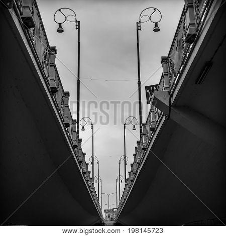 dark shadowy photo symmetry of a city concrete bridge