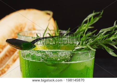 Delicious and refreshing alcohol beverages with lime pieces, spicy tarragon and ice. Fruity cocktail in a glass with a spoon on a black background. Green herbal drink and cut juicy melon.