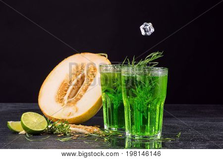 Close-up of delicious and refreshing alcoholic beverages with lime pieces, spicy tarragon and ice cubes. Fruity cocktails in a tall glasses on a black background. Green herbal drink and a juicy melon.