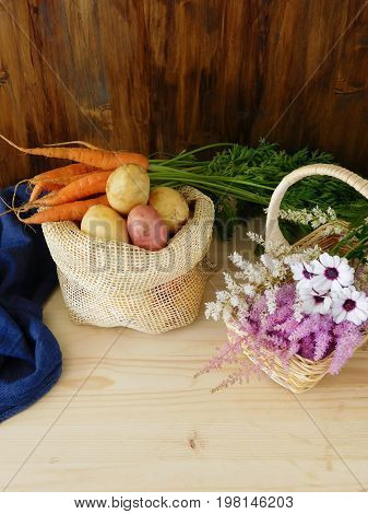 Potatoes in a sack, carrots and flowers in a wicker basket. Freshly picked harvest