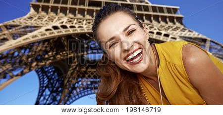 Portrait Of Happy Young Woman In Front Of Eiffel Tower In Paris