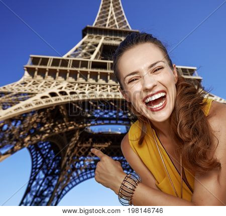 Happy Woman Pointing On Eiffel Tower In Paris, France