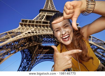 Smiling Woman Framing With Hands Against Eiffel Tower In Paris