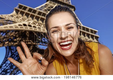 Smiling Woman Showing Ok Gesture In Front Of Eiffel Tower, Paris