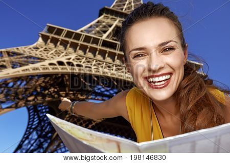 Woman Holding Map And Pointing In Front Of Eiffel Tower, Paris