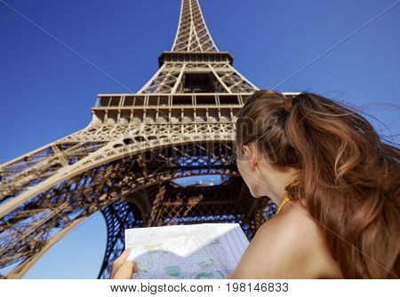 Touristy without doubt but yet so fun. Seen from behind young woman with map against Eiffel tower in Paris France