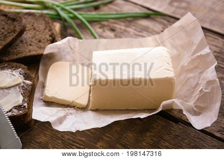 Piece of unwrapped butter on wooden table