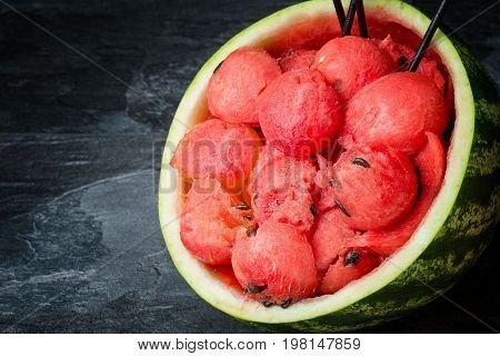 Colorful, fresh, juicy cut watermelon on a black background. Red ripe watermelon scoops with seeds. A cut watermelon with black straws. Refreshing and healthful summer fruits and berries. Copy space.
