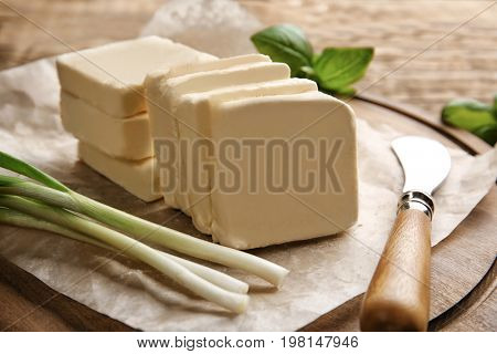 Cutting board with unwrapped sliced butter, knife and greens, closeup