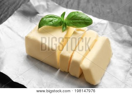 Piece of unwrapped sliced butter and basil leaves on dark table