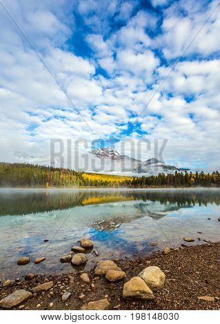 Patricia Lake among the firs and pines. The water reflects the snowy peak of the Pyramid Mountain. Indian Summer in Canada. The concept of extreme and ecotourism