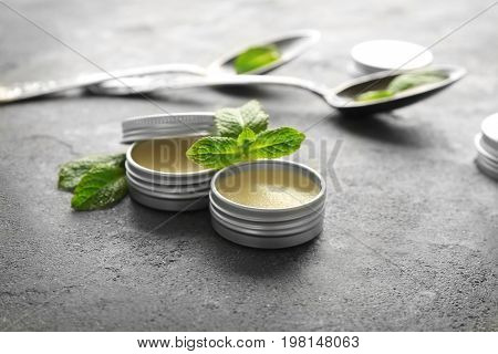 Containers with lemon balm salve and leaves on table