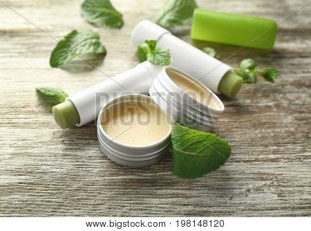 Cosmetic products with lemon balm on wooden background