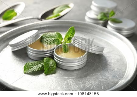 Containers with lemon balm salve and leaves on metal tray