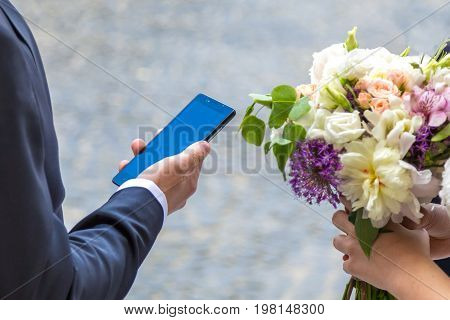Groom holds the phone in the river and the bride holds a wedding bouquet.