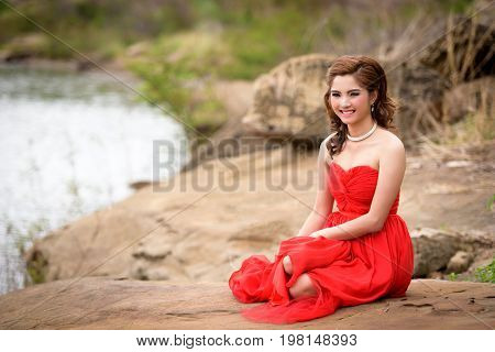 Close Up Beautiful Woman Wear Red Evening Dress Happy Smile Sitting On A Rock In The Woods.