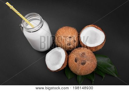 Coconuts with fresh green leaves and a mason jar of coconut milk on a black background. Healthy food. Tropical coconuts and coconut milk in a mason jar with yellow straw. Exotic fruits.