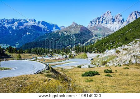 Autumn in the Tirol. Impressive ridge of dolomite rocks. Sharp turn of the road on the Sella Pass, Dolomites. The concept of ecological and extreme tourism