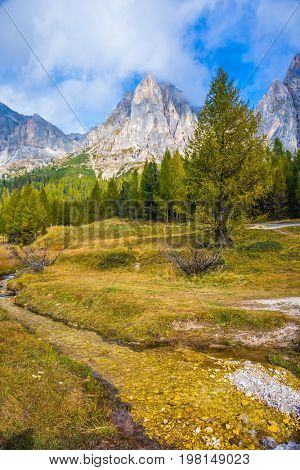 The concept of ecological and extreme tourism. Sharp rocks surround the grassy valleys. A cold fast spring flows through the valley. The dizzying Dolomites
