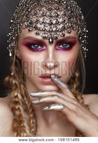Fashion portrait of beautiful young model with professional purple makeup, perfect skin and accessory from hauberk on the head. Red and lilac smoky eyes. Young amazon warrior.