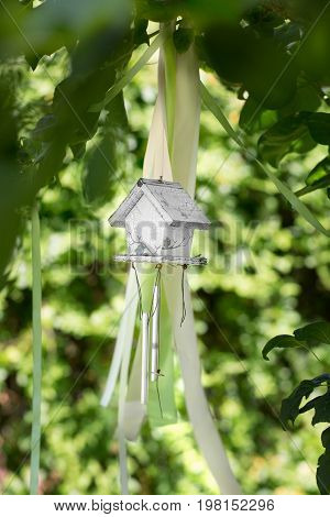 A wooden gray birdhouse on the natural background. The beautiful hand wood shelter for birds to spend the winter. The small nesting box for birds on the blurred background.