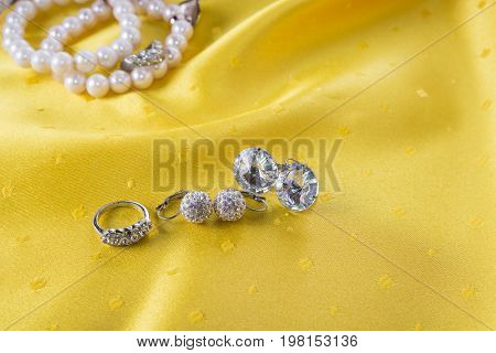Custom jewelry like earings and ring on the yellow background