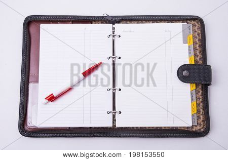 Open notepad carring case with pen on the white background