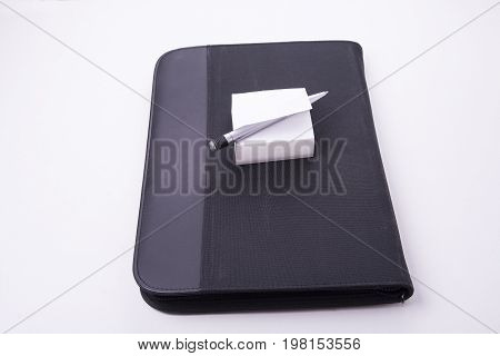 Closed notepad carrying case with paper and pen in white