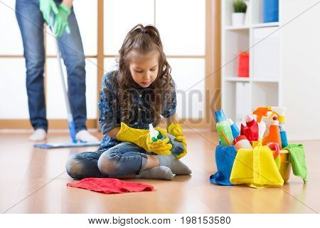 Cute child little girl cleanses a floor in nursery at home