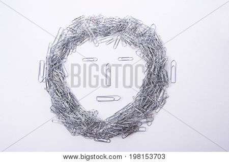 Face make from paper clips on white background