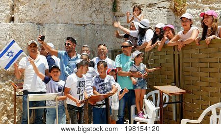 Jerusalem, Israel - May 25, 2017: Israeli family is singing and being happy celebrating the Jerusalem Day near Western Wall - Wailing Wall or Kotel - the most sacred place for all jews on the planet.