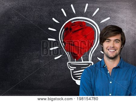 Digital composite of Man standing next to light bulb with crumpled paper ball in front of blackboard